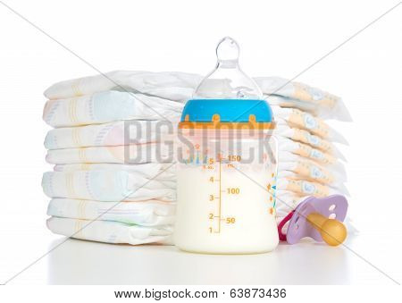 Stack Of Diapers Nipple Soother And Baby Feeding Bottle With Milk