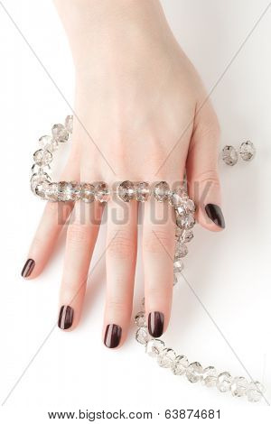 Closeup image of woman hand with beautiful manicure holding glass crystal necklace