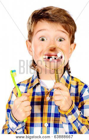 Little funny boy smiling through a magnifying glass, showing his teeth. Healthcare. Isolated over white.