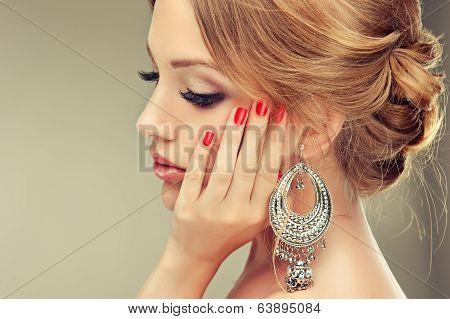 Beautiful model with red manicure and elegant hairstyle