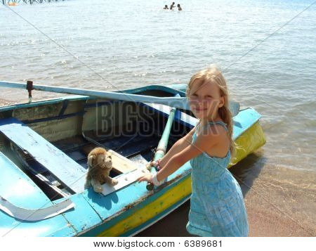 The little girl in a blue dress stands near the boat