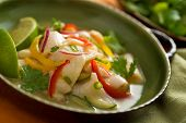 stock photo of yellow-pepper  - A freshly made white fish ceviche with red onion red pepper yellow pepper cucumber lime and green onion - JPG