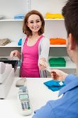 stock photo of over counter  - Client Handing Over Credit Card To A Happy Female Cashier - JPG