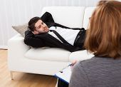 picture of recliner  - Business man reclining comfortably on a couch talking to his psychiatrist explaining something - JPG