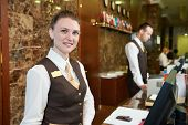 foto of receptionist  - Happy female receptionist worker standing at hotel counter - JPG