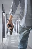 foto of terrorist  - Man holding gun against an corridor background - JPG