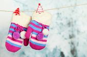 stock photo of clotheslines  - Striped mittens hanging on clothesline on bright background - JPG