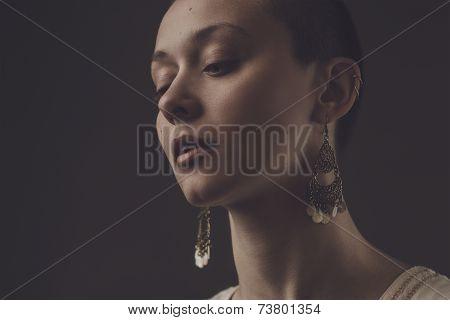 beautiful bald-headed girl over dark grey background