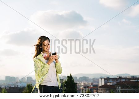 Female Athlete With Smartphone Messaging