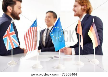 Several flags on negotiation table, three business people discussing in the background