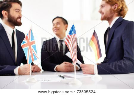 American, British and German flags on the desk, three business partners negotiating in the background
