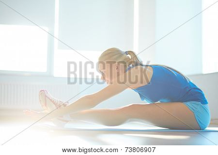 Portrait of young woman doing stretching exercise