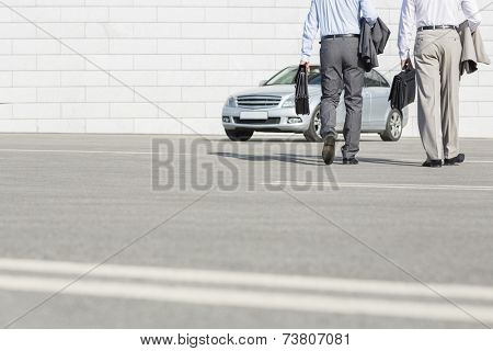 Low section of businessmen carrying briefcases while walking towards car on street
