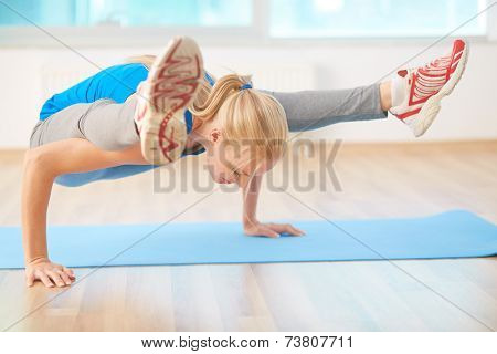 Agile blond girl doing yoga exercise in gym