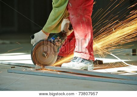Construction builder worker with grinder machine cutting metal bar at building site