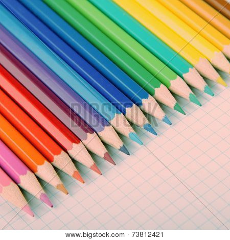 Multicolored Crayons On White Squared Paper Background.