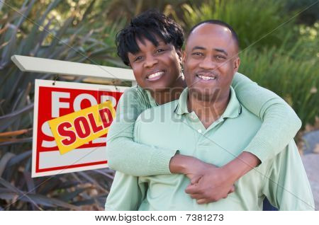 Happy Couple And Real Estate Sign