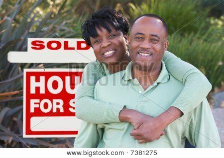 Casal feliz e sinal de imóveis