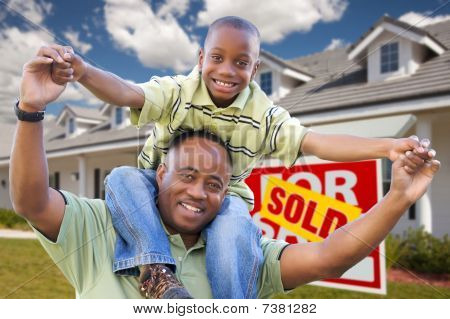 Father And Son In Front Of Real Estate Sign And Home