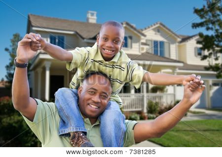 Playful Father And Son In Front Of Home