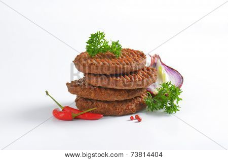 side view of four stacked grilled burgers with fresh onion and chili pepper