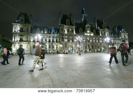 PARIS, FRANCE - SEPTEMBER 13, 2013: People on the Place de l'Hotel-de-Ville against the City Hall in evening. The City of Paris's administration has been located on the same location since 1357