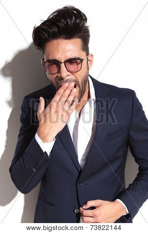 Tired business man yawning while holding one hand to his mouth and the other on his jacket, on white background