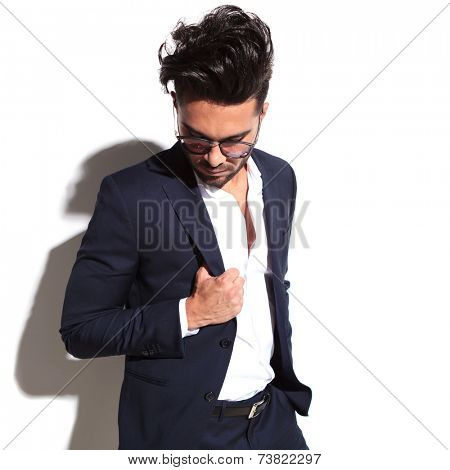 Cool business man wearing sunglasses looking down while pulling his jacket, on white background