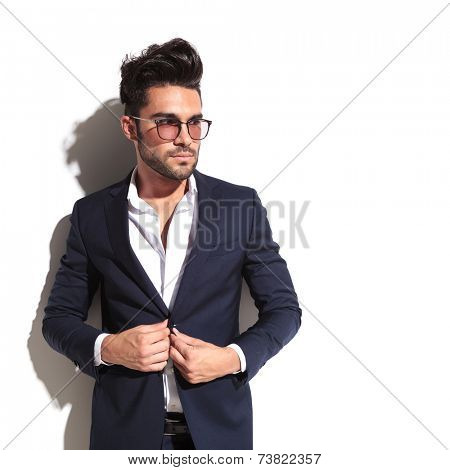 Handsome business man leaning on a white wall while unbuttoning his jacket, looking away