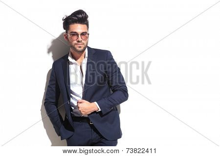 Attractive business man pulling his jacket while leaning on a white wall with one hand in his pocket