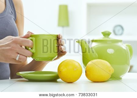 High key still life with tea kettle mug and lemon, pastel colors. Close up hand with ring, holding cup, copyspace.