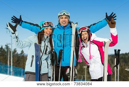 Half-length portrait of group of alpine skier friends with hands up. Concept of cute winter sport and funny vacations with friends
