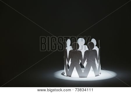 Team of paper doll people holding hands, isolated on black. Concept of friendship and support