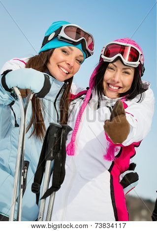 Half-length portrait of two female skier friends thumbing up