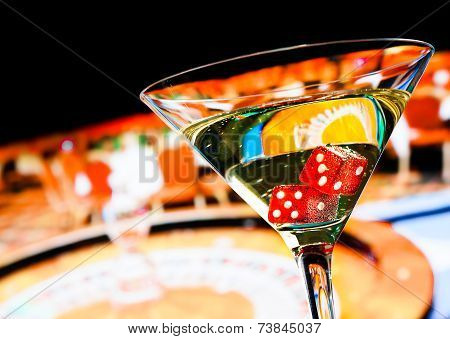 Red Dice In The Cocktail Glass In Front Of Roulette Wheel