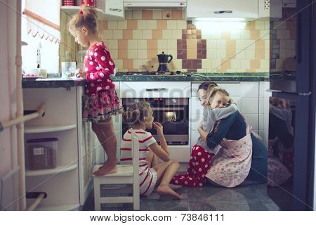 Mother with three kids cooking holiday pie in the kitchen to Mothers day, casual lifestyle photo series in real life interior