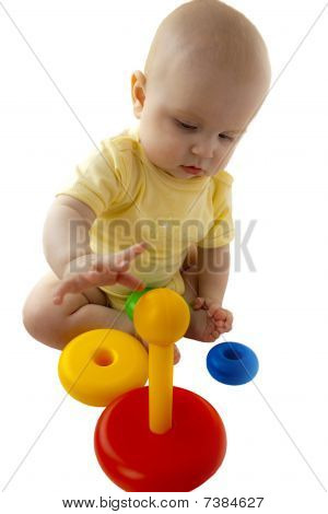 The happy baby smiles and sits next there is a toy a pyramid