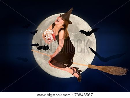 Witch flying on broomstick with gift box. Halloween moon.