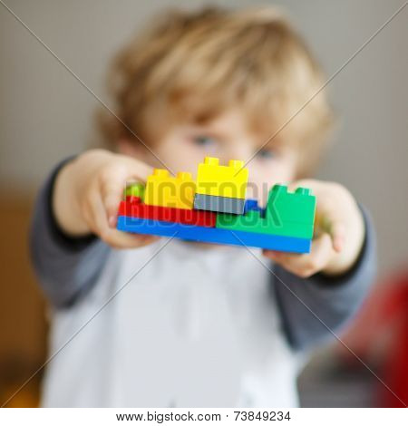 Happy Little Kid Boy Playing With Construction Blocks With Created Tower.