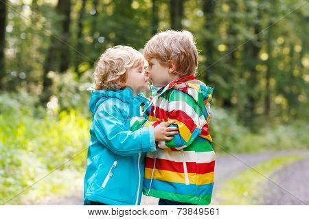 Two Little Sibling Boys In Colorful Raincoats And Boots Walking Through Autumn Forest