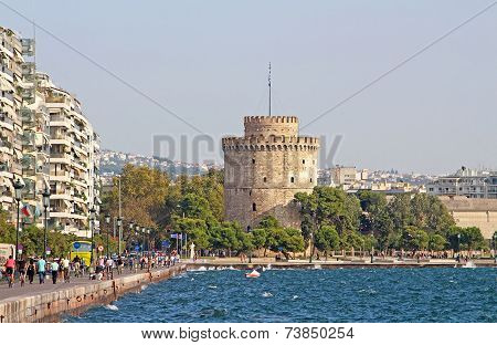 White Tower And Unidentified People Are Walking On The embankment