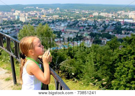 Little Girl Swelling Soap Bubbles Out Of City