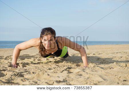 Woman doing push ups on a beach on a warm summer evening.