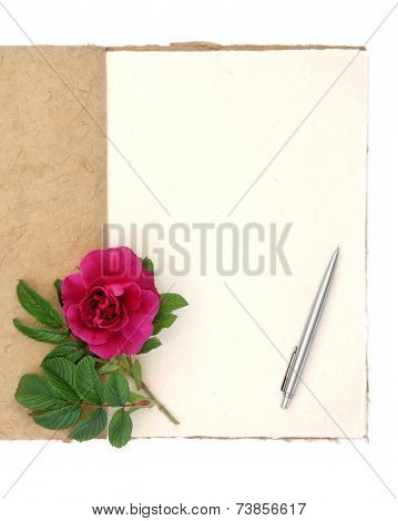 Old vintage notebook with red rose and writing pen over white background. Rosa rugosa.