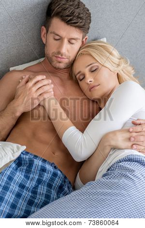 Romantic Middle Age Sexy Couple Sleeping on Bed with Gray Wall Background.