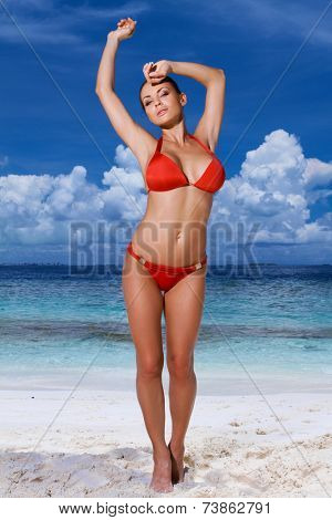 Sexy young woman in a red bikini at the beach standing with her arms raised and a seductive expression with an ocean backdrop