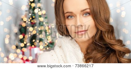 happiness, winter holidays and people concept - close up of smiling young woman in white warm clothes over christmas tree lights background