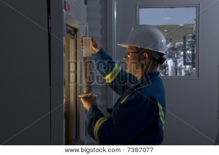 Petroleum Worker Measuring Chemicals