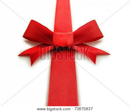 Red ribbon bow with ribbon extending from front to back. Isolated on white.