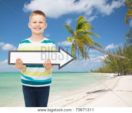 advertising, direction, summer, travel and childhood concept - smiling little boy with white blank arrow over tropical beach background